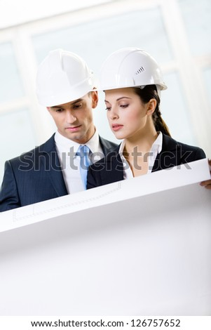 Two engineers looking at the blueprint and discuss their cooperation - stock photo