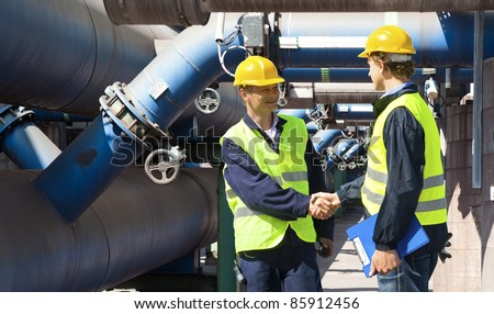 Two engineers meeting outside at the piping of an industrial waste water cleaning facility - stock photo