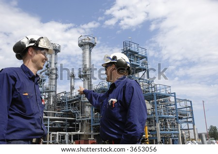 two engineers, one pointing towards large oil refinery, hard-hats and protective clothing - stock photo
