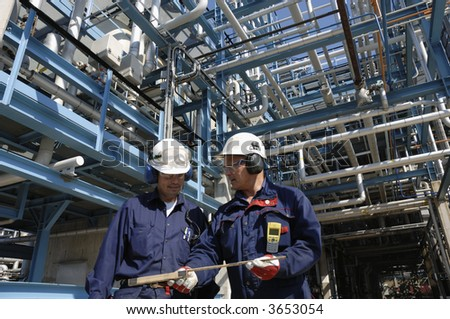 two engineers with hard-hats standing in front of refinery and miles of pipelines - stock photo