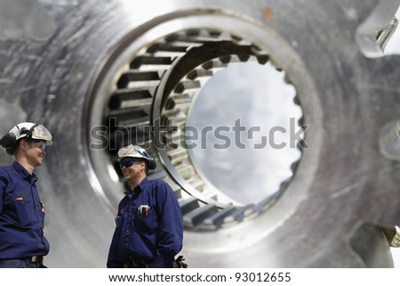 two engineers, workers in hardhat, giant gearwheel shaft in background - stock photo