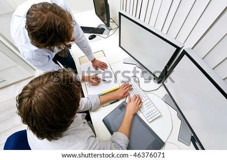 Two engineers, working together in an office, one explaining something to the other - stock photo