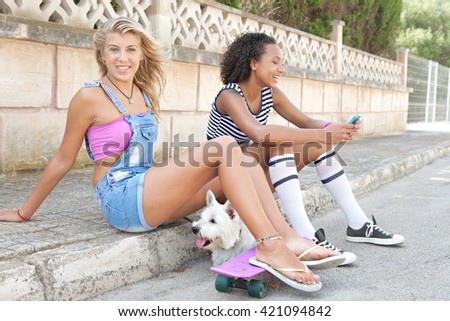 Two ethnically diverse teenager girls friend together in a suburban street, carrying a white dog pet, looking and smiling at camera, outdoors. Active adolescent young women with animal on holiday. - stock photo