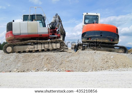 Two excavators on a pile of sand - stock photo