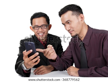 Two excited Asian businessmen watching something on smartphone, isolated on white background - stock photo