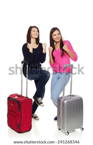 Two excited girls friends in full length with travel suitcases celebrating success, isolated on white background. - stock photo