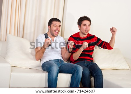 Two excited men sitting on couch and watching favorite team soccer with goal - stock photo