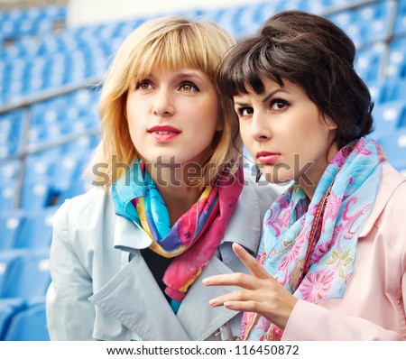 two excited  women fans watching  competition or concert in stadium - stock photo