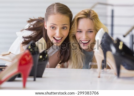 Two excited women looking at heel shoes in shoe store - stock photo