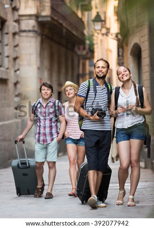 Two excited young tourist couples with travel bags walking through the city. Selective focus - stock photo