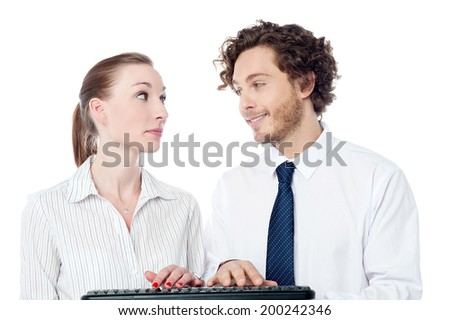 Two executives typing on keyboard, looking each others