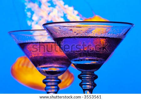 Two exotic grape martini cocktails in a night club setting.