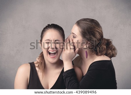 Two fancy dressed actress girls with long hair and make up whispering in front of grey urban background concept. - stock photo