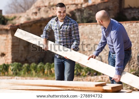 Two farmers working with construction materials outdoors  - stock photo