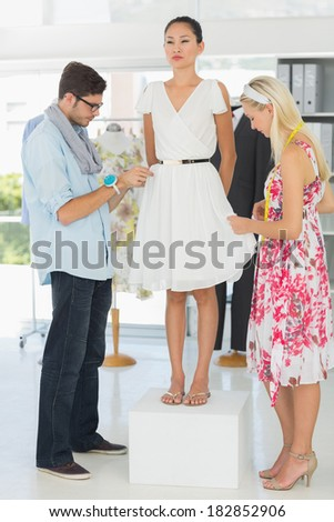 Two fashion designers adjusting dress on model in the studio
