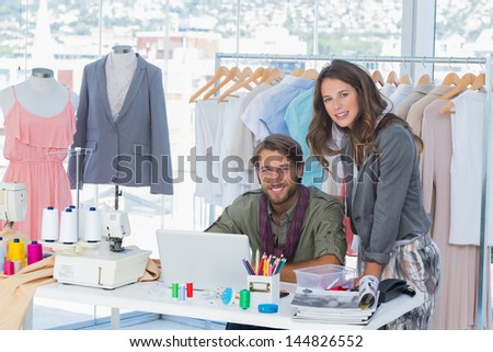 Two fashion designers in a creative office looking at camera - stock photo