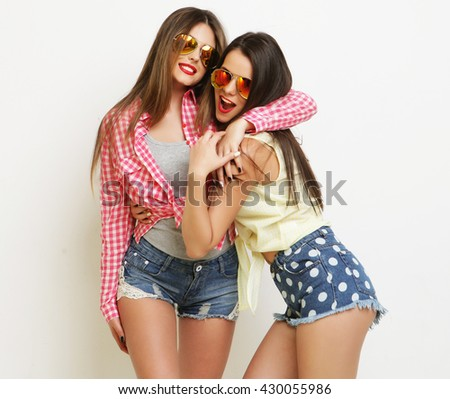 Two fashion laughing painted girl friends hugging and having fun - stock photo
