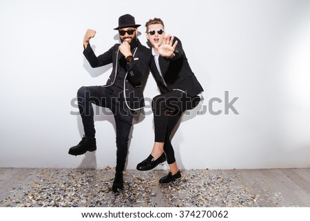 Two fashion man dancing on white background - stock photo