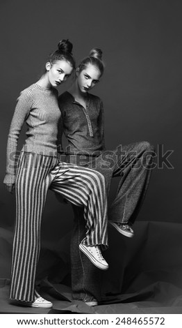 Two fashion models pose on gray background