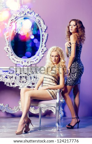 Two fashion models posing in glamorous interior