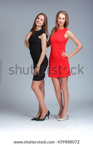 Two fashion models posing in stusio on grey background