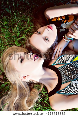 two fashion models  yong sexy face, in color dress posing on grass background - stock photo