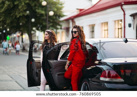 Two Fashionable And Beautiful Girlfriends Going Outside From Black Luxury Car At Street Stylish Confident