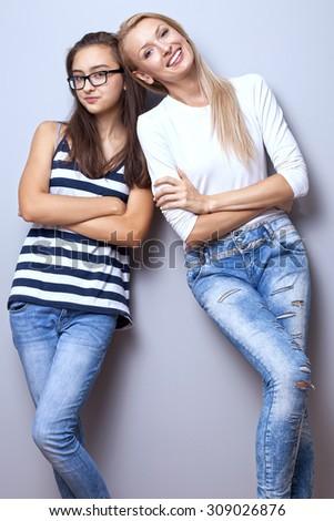 Two fashionable beautiful young girls posing, smiling, wearing jeans. Girls looking at camera. Studio shot.  - stock photo