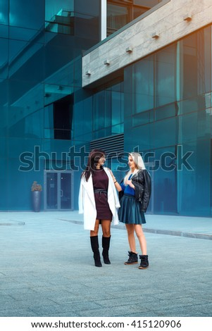 two fashionable sexy ladies brunette and blonde looking at each others outdoors - stock photo