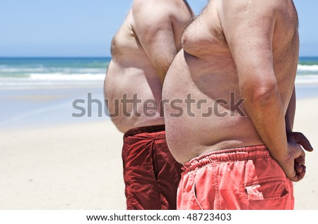 Two fat men on the beach - stock photo