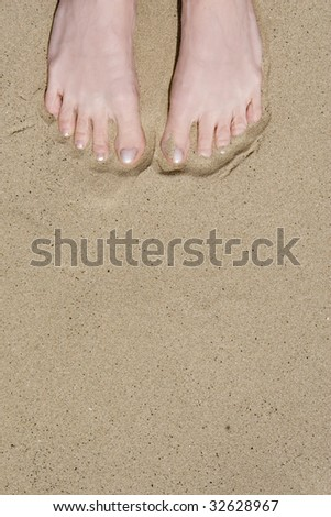 Two feet in sand at the beach, shot  portrait - stock photo