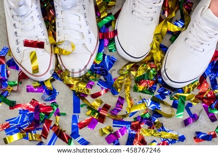 Two feet in white shoes between multicolored festive confetti on the grey floor