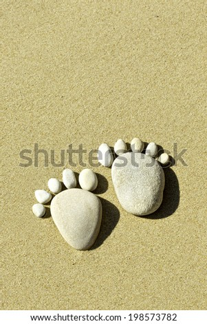 two feet made out of stones indicating footprints in the sand - stock photo