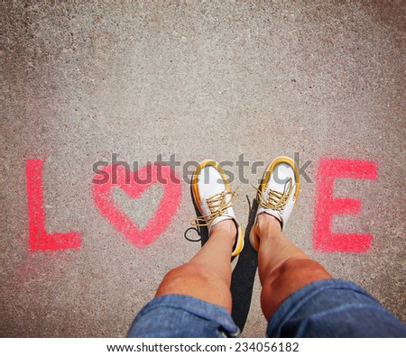 two feet making a sign for the letter V in the word love - stock photo