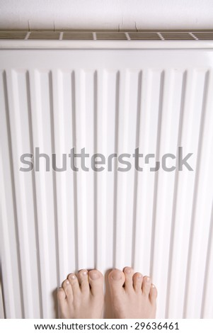 Two feet placed on a heater for warmth  shot portrait - stock photo