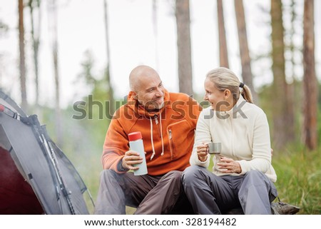 Two fellow campers talking to each other and drinking tea by a tent in the forest