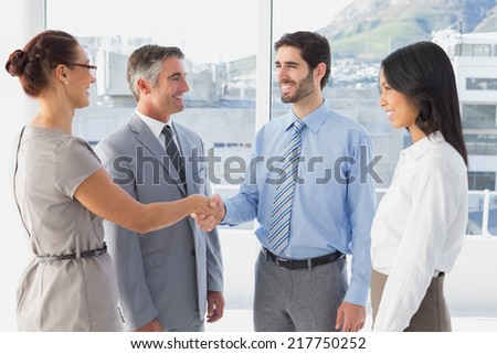 Two fellow employees shaking hands with other workers - stock photo