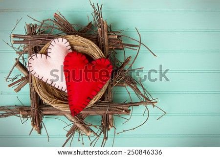 Two felt hearts in a rustic wooden nest on a retro turquoise background - stock photo