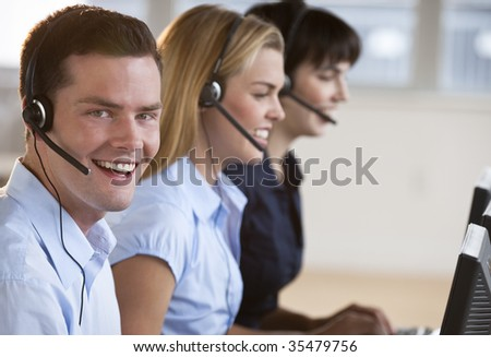 Two female and one male customer service representatives smiling.  They are working on computers and are wearing headsets. The male is looking directly at the camera. Horizontally framed shot.