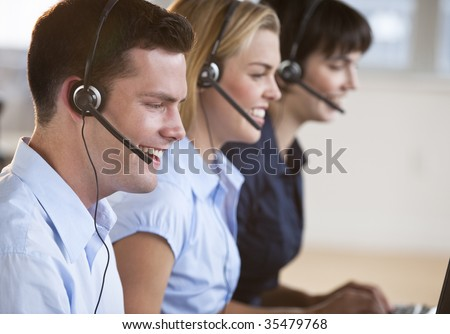 Two female and one male customer service representatives smiling.  They are working on computers and are wearing headsets. Horizontally framed shot.