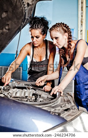 Two female auto mechanic repairing a car, working on the transmission. - stock photo