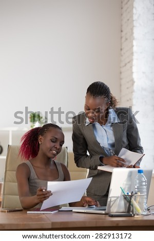 Two female colleagues working together - stock photo