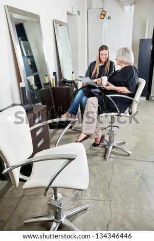 Two female customers waiting at hair salon - stock photo