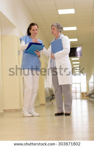 Two female doctors standing watching patient files in hospital corridor - stock photo