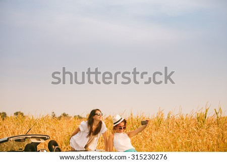 Two female friends beside cabriolet taking selfies with smartphone