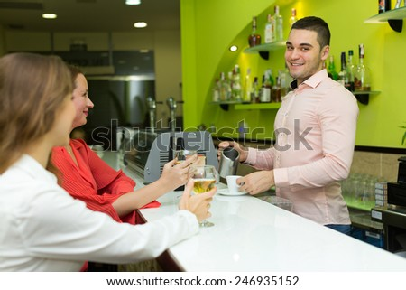 Two female friends chatting and drinking wine at bar - stock photo