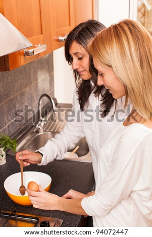 Two Female Friends Cooking in the Kitchen - stock photo