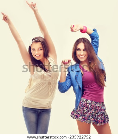 Two female friends dancing and singing. - stock photo