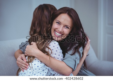 Two female friends embracing each other at home