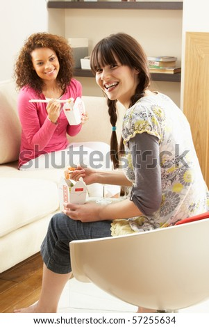Two Female Friends Enjoying Chinese Takeaway Meal At Home - stock photo